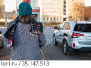 Woman paying for gasoline via credit card machine, self service petrol station without staff, rear view. Стоковое фото, фотограф Кекяляйнен Андрей / Фотобанк Лори