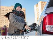 Attractive woman holding fuel pump nozzle with filling diesel in her car at self-service petrol station. Стоковое фото, фотограф Кекяляйнен Андрей / Фотобанк Лори