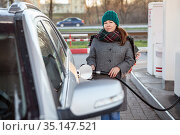 Female driver refueling car at self-service gas station, woman in coat and warm hat holding hose with nozzle and looking at camera. Стоковое фото, фотограф Кекяляйнен Андрей / Фотобанк Лори