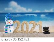 Merry Christmas. Happy snowman and lettering 2021 in sand on the beach. Стоковое фото, фотограф Сергей Молодиков / Фотобанк Лори