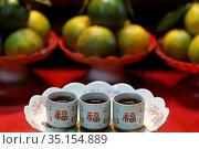 Khanh Van Nam Vien Taoist pagoda. Altar with offerings. Tea and fruits... Стоковое фото, фотограф Fred de Noyelle / Godong / age Fotostock / Фотобанк Лори