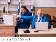 Old male boss and his young male assistant in bullying concept. Стоковое фото, фотограф Elnur / Фотобанк Лори