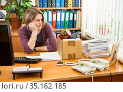 Woman just lost his job sitting at teh desk with his head down feeling depressed. Стоковое фото, фотограф Кекяляйнен Андрей / Фотобанк Лори