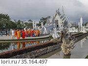 Группа буддистских монахов фотографируются уу Белого храма (Wat Rong Khun) облачным утром . Чианг Рай, Таиланд (2018 год). Редакционное фото, фотограф Виктор Карасев / Фотобанк Лори