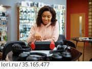 Woman looking on headphones, speaker systems store. Стоковое фото, фотограф Tryapitsyn Sergiy / Фотобанк Лори