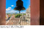 View of the Granada city through the arch of the bell tower of La Merced Church along the street Calle Real Xalteva with Iglesia de Xalteva catholic church at the background. Nicaragua. Стоковое фото, фотограф Николай Коржов / Фотобанк Лори