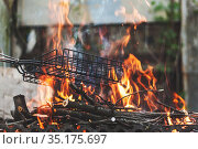 Firewood and branches for coals burn out in the brazier. Retro vintage effect. Keep the grill grate over the fire. Стоковое фото, фотограф Tetiana Chugunova / Фотобанк Лори