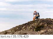 young man on hiker resting on a rocky peak against the background of blue sky on a summer day. Стоковое фото, фотограф Акиньшин Владимир / Фотобанк Лори