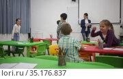 Happy pupils chattering sitting at lesson in elementary school. Стоковое видео, видеограф Яков Филимонов / Фотобанк Лори
