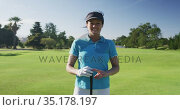 Portrait of female caucasian golf player smiling while standing with golf club at golf course. Стоковое видео, агентство Wavebreak Media / Фотобанк Лори