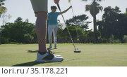 Two caucasian women playing golf wearing face masks one taking shot from bunker. Стоковое видео, агентство Wavebreak Media / Фотобанк Лори