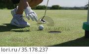 Caucasian woman playing golf reaching for a ball. Стоковое видео, агентство Wavebreak Media / Фотобанк Лори