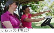 Two caucasian women playing golf riding a golf cart talking and laughing. Стоковое видео, агентство Wavebreak Media / Фотобанк Лори
