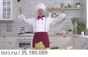 A friendly elderly chef waving his instruments like a conductor in the kitchen. The man is holding a ladle and whisk. Стоковое видео, видеограф Михаил Решетников / Фотобанк Лори