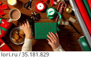 hands packing christmas gift and choosing bow. Стоковое видео, видеограф Syda Productions / Фотобанк Лори