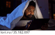 indian man with tablet pc in bed at home at night. Стоковое видео, видеограф Syda Productions / Фотобанк Лори