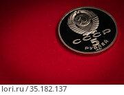 Старые юбилейная монета СССР 5 рублей на красном фоне. Стоковое фото, фотограф Павел Сапожников / Фотобанк Лори