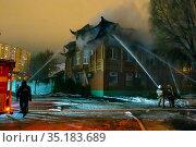 Russia Samara January 2020: EMERCOM employees extinguish a fire at night in winter. Редакционное фото, фотограф Акиньшин Владимир / Фотобанк Лори