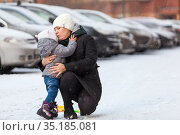 Mother talking with her little child, embracing and kissing after falling dawn on ice at winter season. Стоковое фото, фотограф Кекяляйнен Андрей / Фотобанк Лори