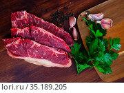 Sliced beef pieces on dark wooden board with parsley leafs and peas of bitter pepper. Стоковое фото, фотограф Яков Филимонов / Фотобанк Лори