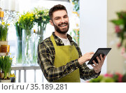 happy male seller with tablet pc at flower shop. Стоковое фото, фотограф Syda Productions / Фотобанк Лори