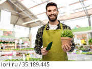 gardener or seller with trowel at flower shop. Стоковое фото, фотограф Syda Productions / Фотобанк Лори