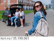 Three girlfriends go on a road trip. Young woman posing with a suitcase. Two girls are sitting on the trunk of a car and watching a map. Стоковое фото, фотограф Михаил Решетников / Фотобанк Лори