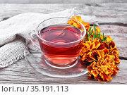 Чай травяной из бархатцев в стеклянной чашке на старой доске. Стоковое фото, фотограф Резеда Костылева / Фотобанк Лори