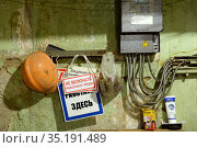 Предупреждающие и запрещающие таблички висят на рабочем месте электрика ЖКХ. Редакционное фото, фотограф Free Wind / Фотобанк Лори