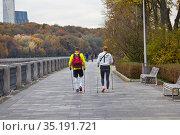 Скандинавская ходьба на набережной и панорамный вид на парк и высотку на Мосфильмовской улице. Редакционное фото, фотограф Victoria Demidova / Фотобанк Лори