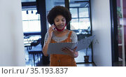 Mixed race businesswoman wearing mask walking going through paperwork in modern office. Стоковое видео, агентство Wavebreak Media / Фотобанк Лори