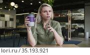 Caucasian businesswoman having a video chat drinking a cup of coffee in modern office. Стоковое видео, агентство Wavebreak Media / Фотобанк Лори
