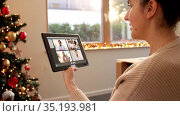 woman with tablet pc has video call on christmas. Стоковое видео, видеограф Syda Productions / Фотобанк Лори