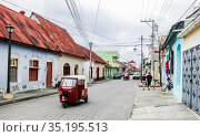 The old part of the city in colonial style with narrow cobblestone streets, red-roofed buildings and pastel houses. Guatemala. Flores, El Peten. Редакционное фото, фотограф Николай Коржов / Фотобанк Лори