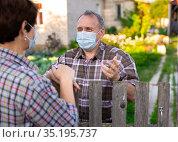 Farm neighbors in protective masks talk at the border of garden plot. Стоковое фото, фотограф Татьяна Яцевич / Фотобанк Лори