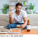 Man eating pizza having a takeaway at home relaxing resting. Стоковое фото, фотограф Elnur / Фотобанк Лори
