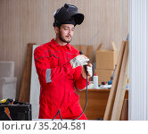 Young repairman with a welding gun electrode and a helmet weldin. Стоковое фото, фотограф Elnur / Фотобанк Лори