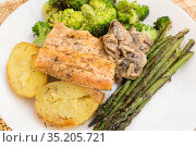 delicious dish of fried river trout fillet with garnish of broccoli, asparagus sprouts, baked potatoes and mushroom sauce. Стоковое фото, фотограф Татьяна Яцевич / Фотобанк Лори
