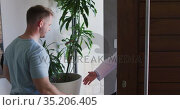 Caucasian man greeting a mixed race male doctor at home. Стоковое видео, агентство Wavebreak Media / Фотобанк Лори