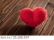 Valentine's day card with a red woolen heart on the brown textured wooden boards. Стоковое фото, фотограф Георгий Дзюра / Фотобанк Лори