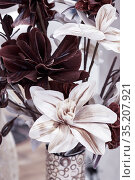 Floral background pattern of chocolate brown earthy and white color with artificial flowers, large elegant lilies in a vase in pastel tone for a postcard. Стоковое фото, фотограф Светлана Евграфова / Фотобанк Лори