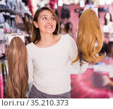 Positive young woman choosing natural wig at specialty boutique. Стоковое фото, фотограф Татьяна Яцевич / Фотобанк Лори