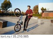 Male bmx biker doing trick, training in skatepark. Стоковое фото, фотограф Tryapitsyn Sergiy / Фотобанк Лори