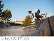 Bmx biker doing trick on ramp in skatepark. Стоковое фото, фотограф Tryapitsyn Sergiy / Фотобанк Лори