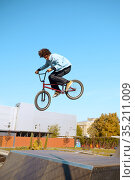 Male bmx biker doing trick on ramp in skatepark. Стоковое фото, фотограф Tryapitsyn Sergiy / Фотобанк Лори