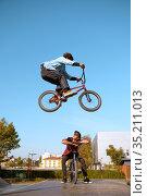 Bmx biker, jump in action, training in skatepark. Стоковое фото, фотограф Tryapitsyn Sergiy / Фотобанк Лори