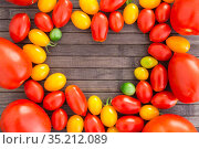 heart made of bright ripe yellow and red cherry tomatoes with place for inscription on wooden table. Стоковое фото, фотограф Татьяна Яцевич / Фотобанк Лори