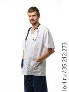Портрет мужчины врача, руки засунул в карманы, на шее висит фонендоскоп, изолировано на белом фоне. Стоковое фото, фотограф Иванов Алексей / Фотобанк Лори