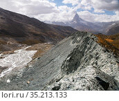 Lateral moraine deposited at edge of Findel glacier. Glacier in retreat with braided river in valley, Matterhorn in distance. Zermatt, Valais, Switzerland. September 2019. Стоковое фото, фотограф Graham Eaton / Nature Picture Library / Фотобанк Лори