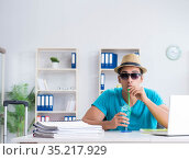 Businessman preparing for vacation in the office. Стоковое фото, фотограф Elnur / Фотобанк Лори